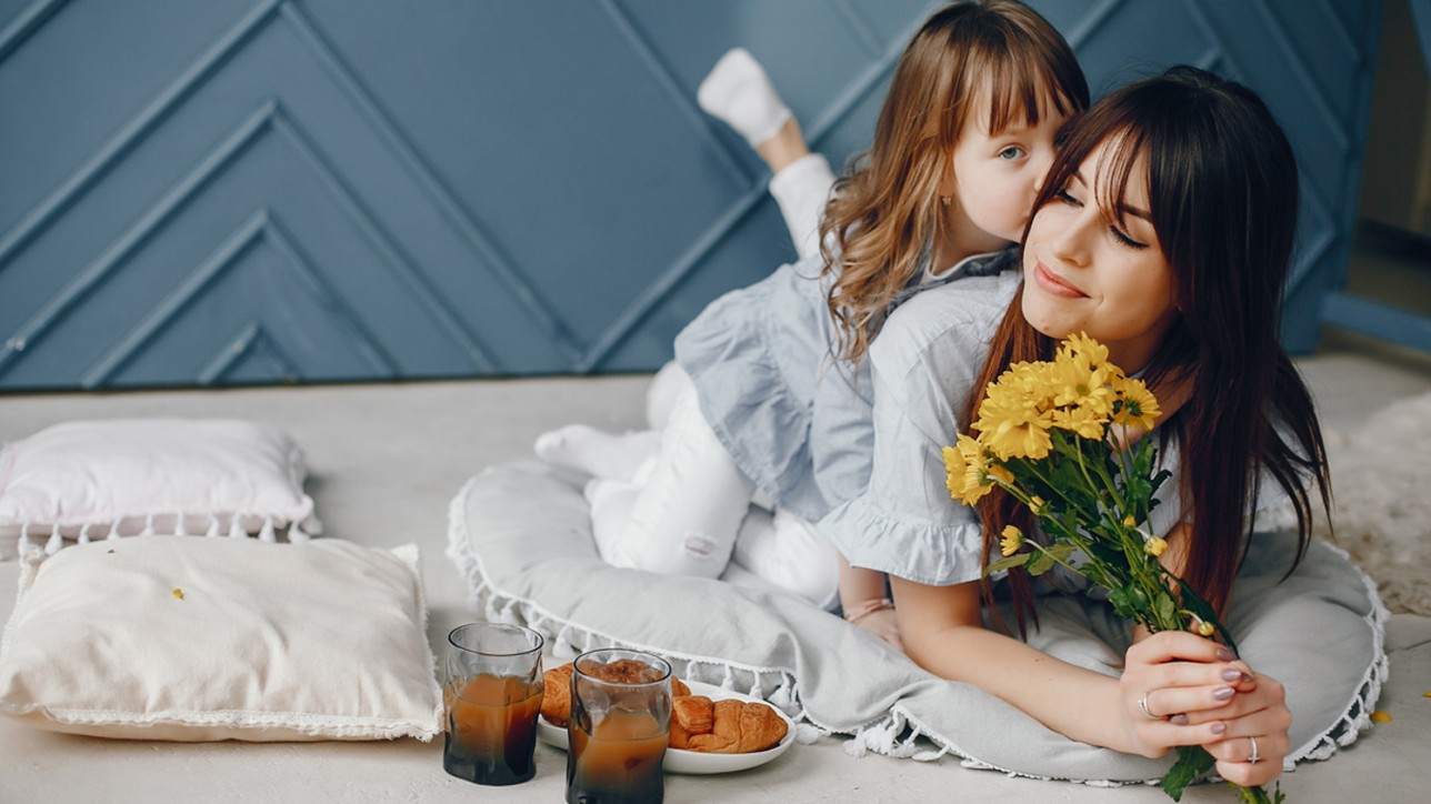 Child give mother flowers. Family at home. Mother's day